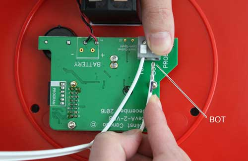 image shows pressing down on white terminals for solinst 107 tlc meter circuit board